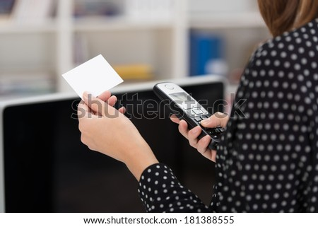 Woman dialing out on her mobile phone using contact details from a blank white business card with copyspace that she is holding in her hand - stock photo