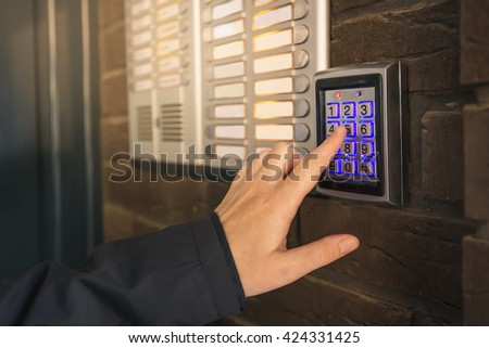 Woman dialing pass code on intercom security keypad to open entrance door of the apartment building. - stock photo
