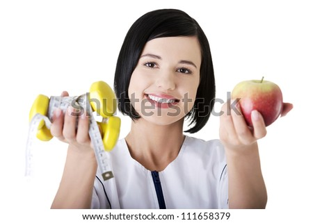 Woman dietician holding apple and dumbbells with measuring tape - stock photo