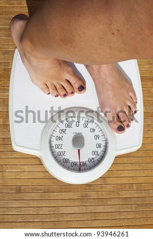 Woman Dieting, close up of woman's bare feet standing on a weight scale