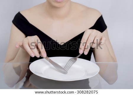 Woman dieting, empty plate - stock photo