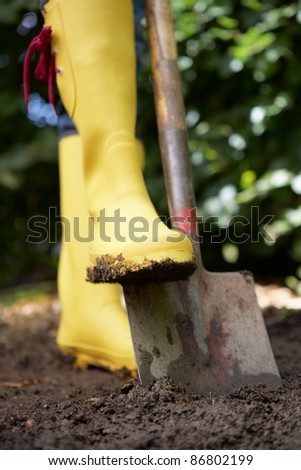 Woman digging in garden - stock photo