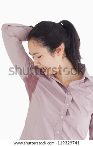 Woman disgusted at her own sweating on white background