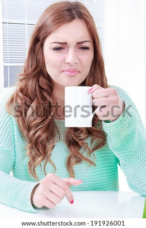 woman disgusting smell of coffee with face expression, girl does not enjoy the smell of drink, woman disliking smell of coffee making negative face expression - stock photo
