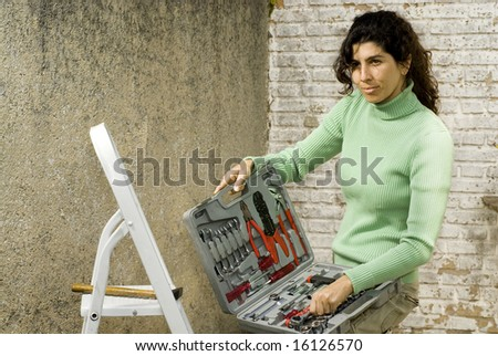 Woman displaying a box of tools with a small smile upon her face. Horizontally framed photo. - stock photo
