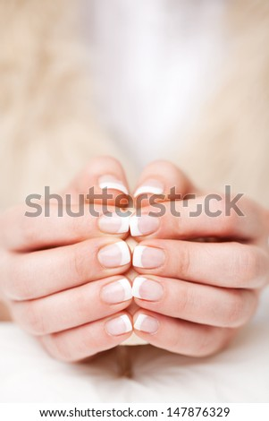 Woman displaying her beautiful manicured fingernails finished in clear gloss varnish holding the tips of her two hands together - stock photo