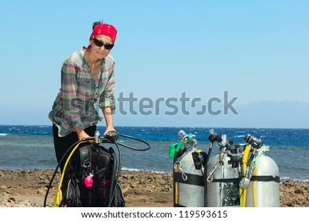 Woman diver prepares for dive - stock photo