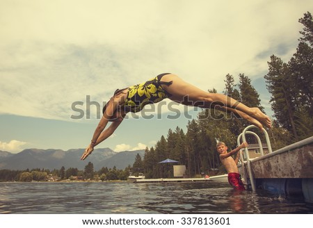 Woman diving off the dock of lake while on summer vacation  - stock photo