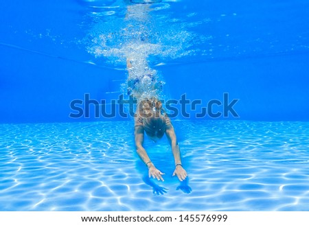 Woman diving underwater in the swimming pool - stock photo