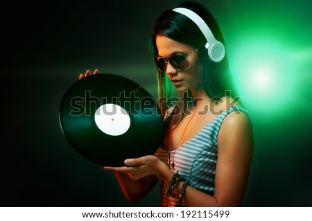 Woman dj portrait with vinyl record and headphones - stock photo