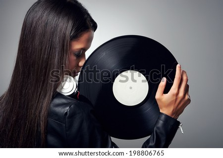 Woman dj portrait with vinyl record and headphones - stock photo
