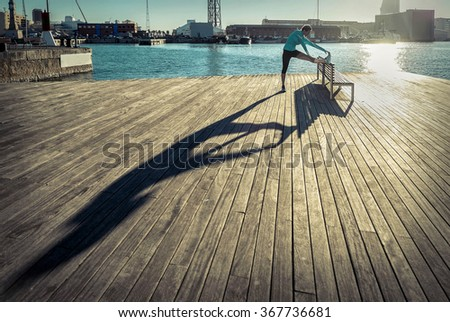 Woman do exercise after running on the wooden pier under sunlight. - stock photo