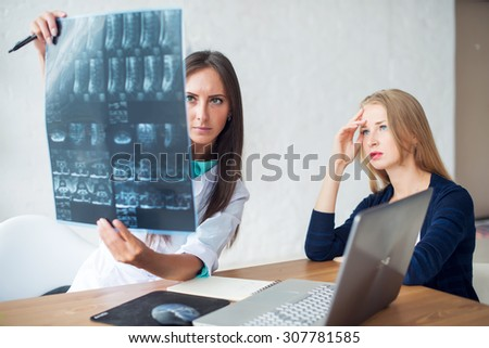 Woman doctor and patient looking at the x-ray or MRI picture in hospital - stock photo