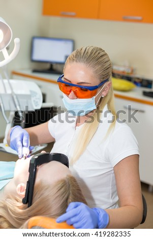 Woman doctor dentist in mask at her working place filling tooth to her patient  - stock photo
