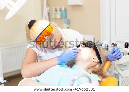 Woman doctor dentist in mask filling tooth to her patient - stock photo