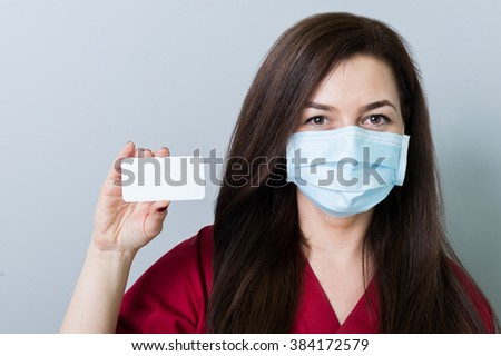 Woman doctor holding a blank white card or paper with copy space - stock photo