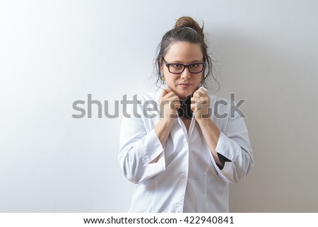 Woman doctor holding up her collar and leaning against a white wall - stock photo
