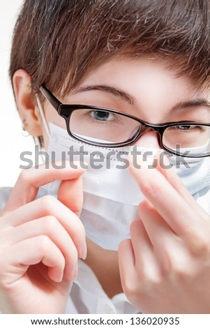 Woman doctor in a mask closeup