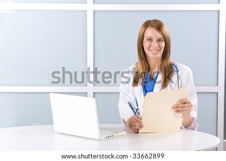 Woman doctor in a modern office at a desk with a laptop - stock photo