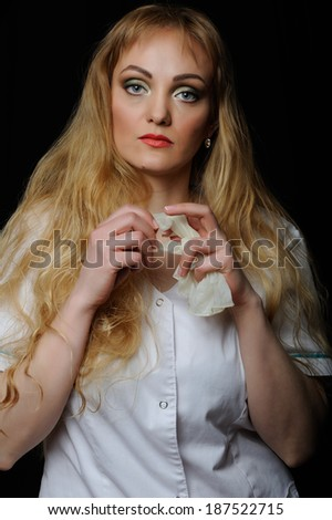 Woman doctor in white coat  holding rubber gloves on  dark background - stock photo