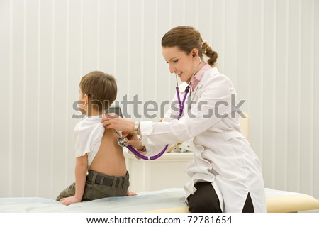 woman doctor listening to heartbeat of 4 years old boy in office - stock photo