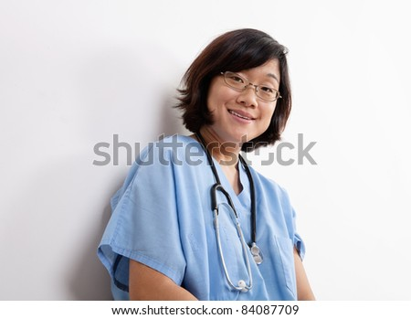 Woman Doctor or Nurse Seated on Floor at Laptop Computer - stock photo