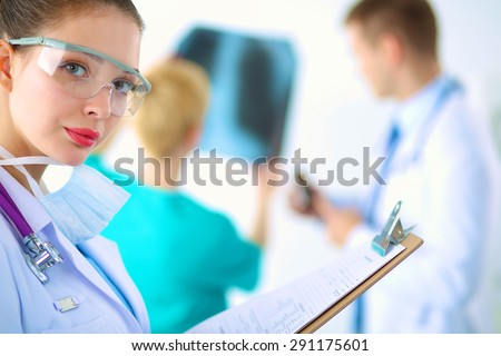Woman doctor standing with folder at hospital  - stock photo