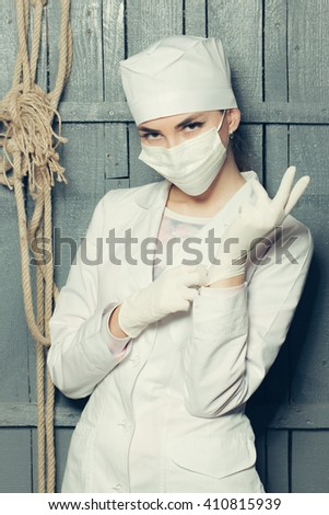 Woman doctor wearing medical gloves in white uniform and mask with rope on wooden wall - stock photo