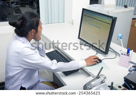 Woman doctor working on computer in office of hospital. Medical staff looking at monitor.