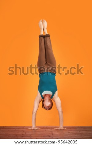 Woman does Adho Mukha Vriksasana yogasana upside down - stock photo