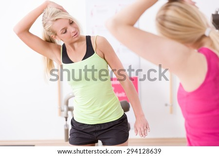 Woman does exercises in a fitness studio with a personal trainer