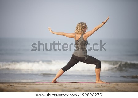 Woman does yoga at the beach of GOA-INDIA - stock photo