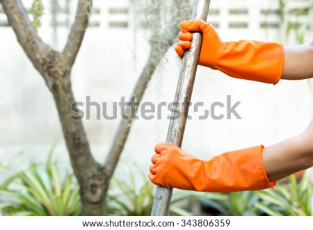 Woman doing a gardening use Shovel with orange gloves - stock photo