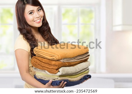 woman doing a housework holding laundry at home - stock photo
