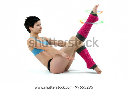 Woman doing aerobic exercises with colorful circles around one leg - stock photo