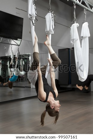 Woman doing anti-gravity exercise in fitness center. - stock photo