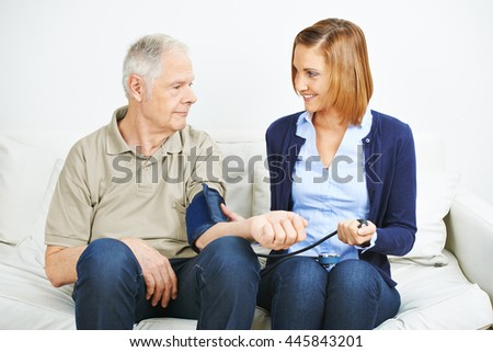 Woman doing blood pressure monitoring for patient in nursing home - stock photo
