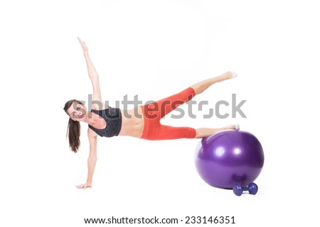 Woman doing body building on a purple fitness ball - isolated on white.