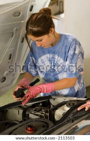 Woman doing car maintenance - stock photo