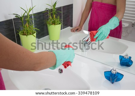 Woman doing chores in bathroom at home, cleaning sink and faucet with spray detergent. - stock photo