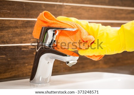 Woman doing chores in bathroom, cleaning modern tap. - stock photo