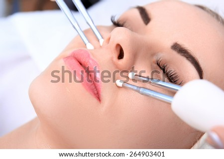 Woman doing cosmetic procedures in spa clinic. - stock photo