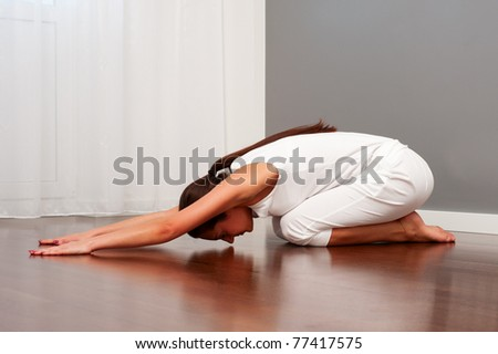 woman doing daily yoga workouts on floor - stock photo