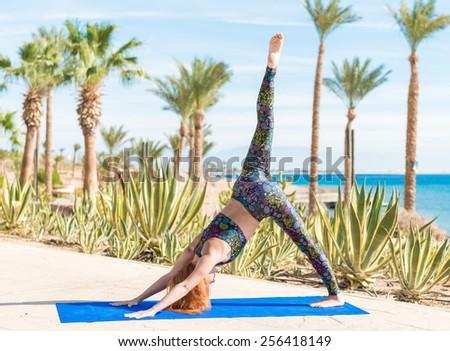 Woman doing down dog yoga asana at the beach - stock photo