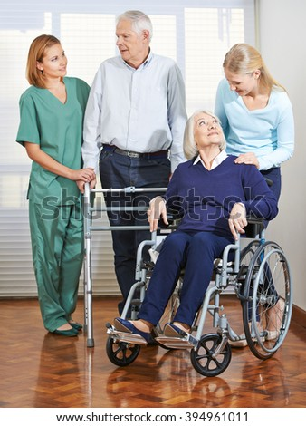 Woman doing elderly care with senior couple at home - stock photo