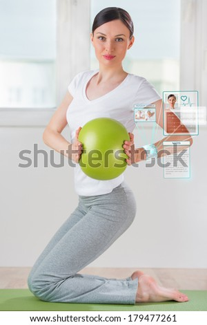 Woman doing exercise with ball wearing smart wearable device with futuristic interface - stock photo