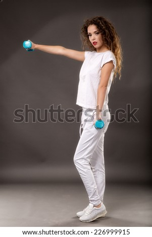 woman doing exercise with dumbbells isolated on gray background - stock photo