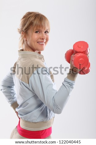 Woman doing exercise with dumbbells view from the back - stock photo