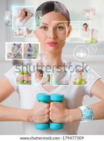 Woman doing exercise with dumbbells wearing smart wearable device with futuristic interface