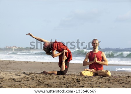 Woman doing exercise yoga with man sit in pose lotus near by - stock photo